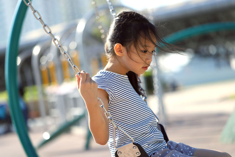 Cute Girl Swinging In Playground