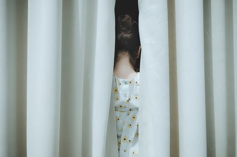 Close-up of woman standing by curtain