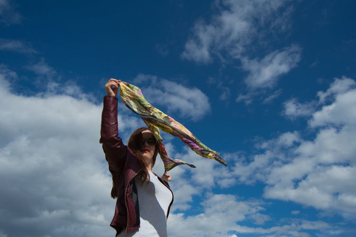 Arms Raised Cloud - Sky Day Girl Portrait Hairstyle Holding Human Arm Leisure Activity Lifestyles Low Angle View Nature One Person Outdoors Real People Scarf Sky Springtime Standing Three Quarter Length Waist Up Wind Wind Motion Women Young Adult Young Women