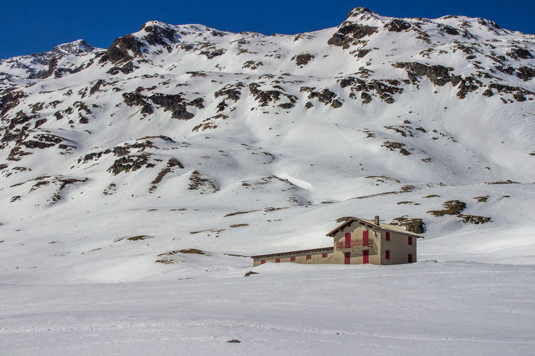 House on snowy hill during sunny day