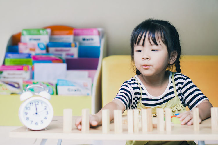 Cute girl playing with block shape at home