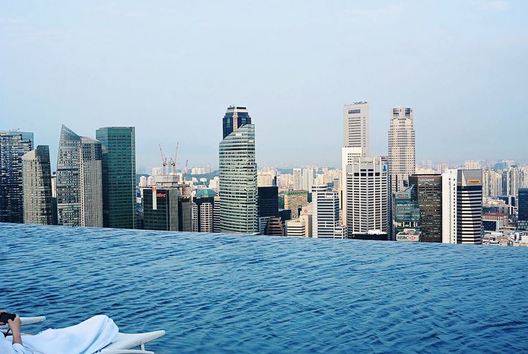 Low Section Of Man Resting By Swimming Pool At Marina Bay Sands Against City