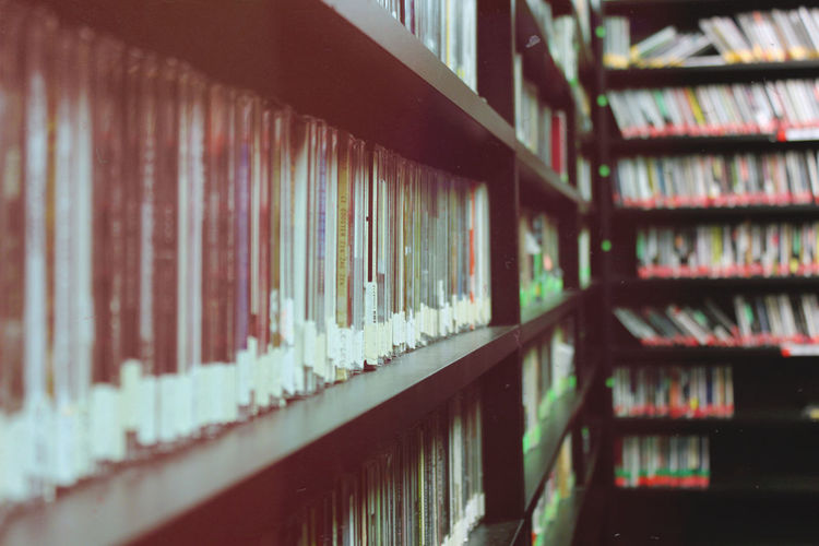 Compact Discs Arranged On Shelf In Library