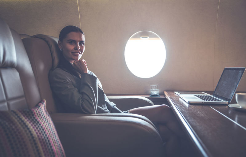 Portrait of smiling businesswoman sitting in airplane