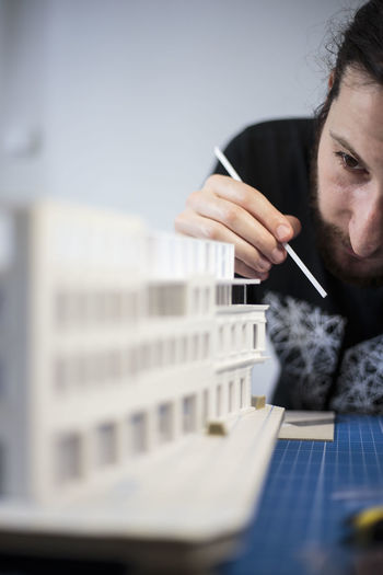Young man preparing architectural model on table