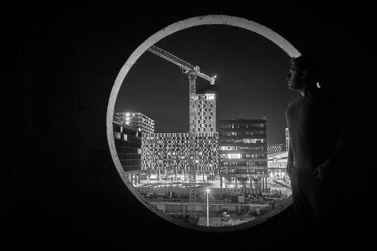 Man Looking At Illuminated Cityscape Through Window