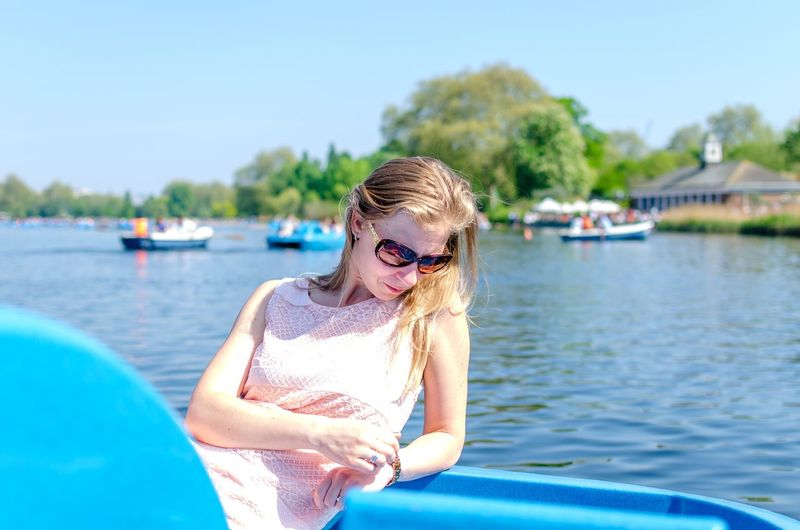 Woman Sitting In Boat Over Lake