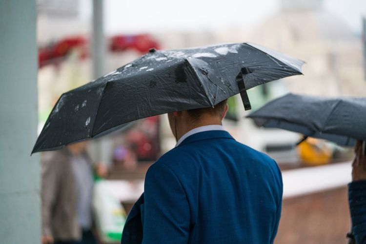 Man With Umbrella Walking On Wet Street