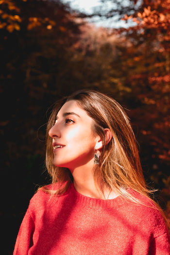 Portrait of beautiful young woman looking away during autumn