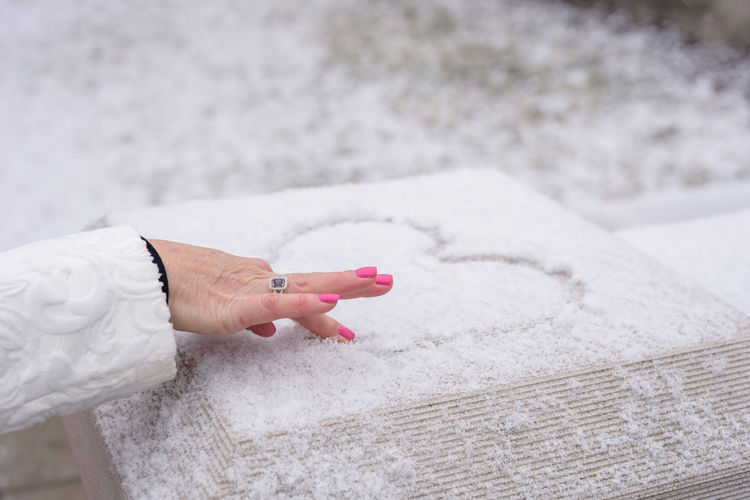 Cropped hand of woman making heart shape on snow