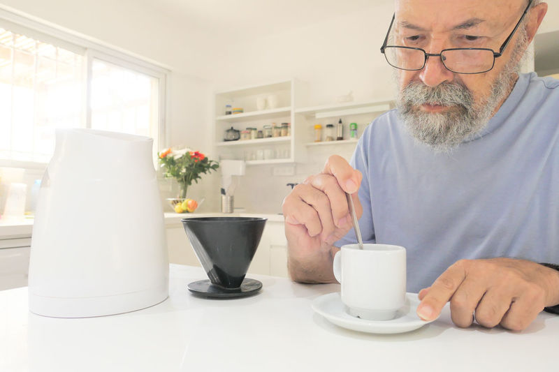 Midsection of man with coffee cups on table