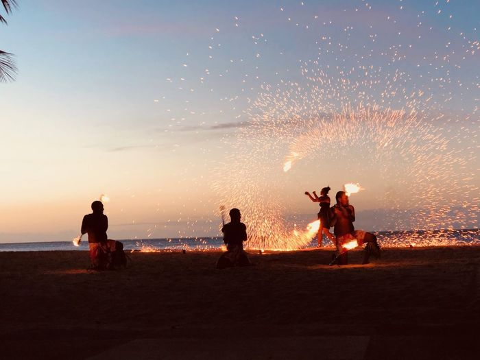 Fire Dancers On Beach Against Sky During Sunset
