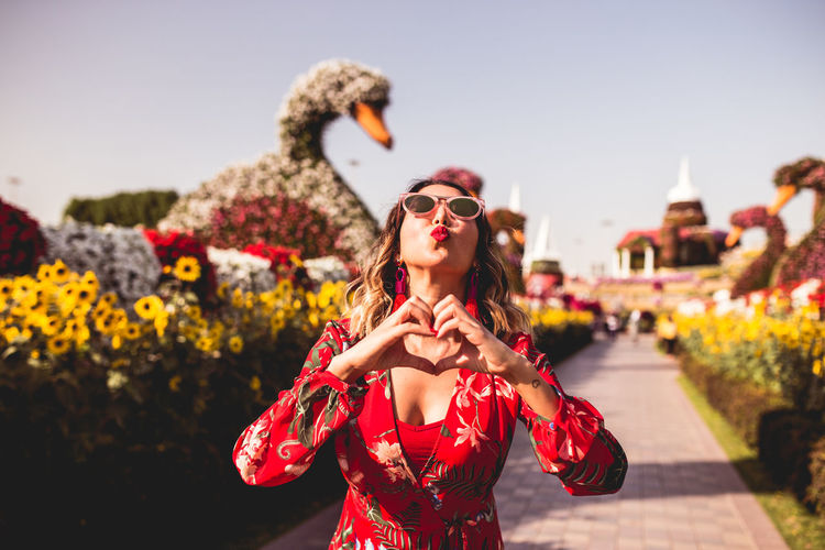 Woman wearing sunglasses making heart shape with hands while puckering lips outdoors