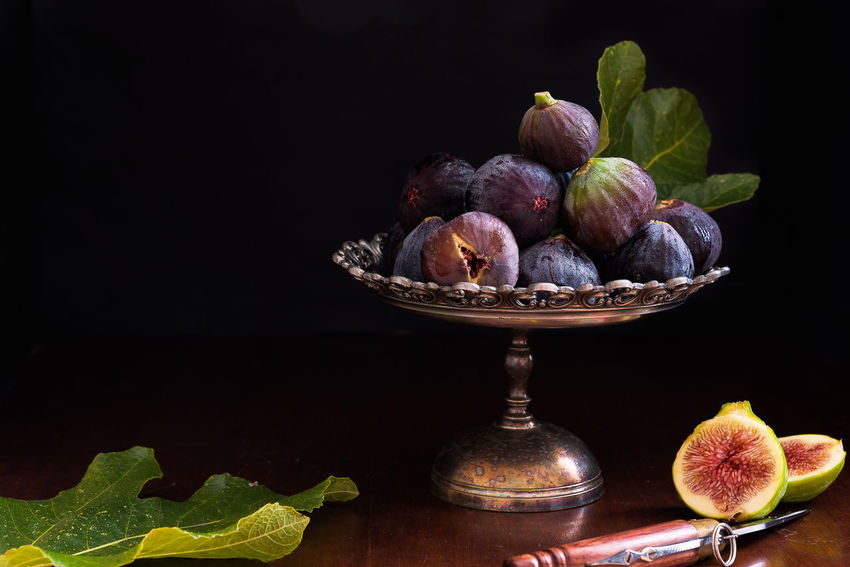 black and white figs on metal dish; still life with leaves and knife Autumn Cut Dessert Dish Knife Nature Black Background Delicious Fall Fig Food And Drink Freshness Fruit Healthy Eating Leaf Light And Dark Metal No People Organic Ripe Still Life Summer Sweet Food Table Vitamin