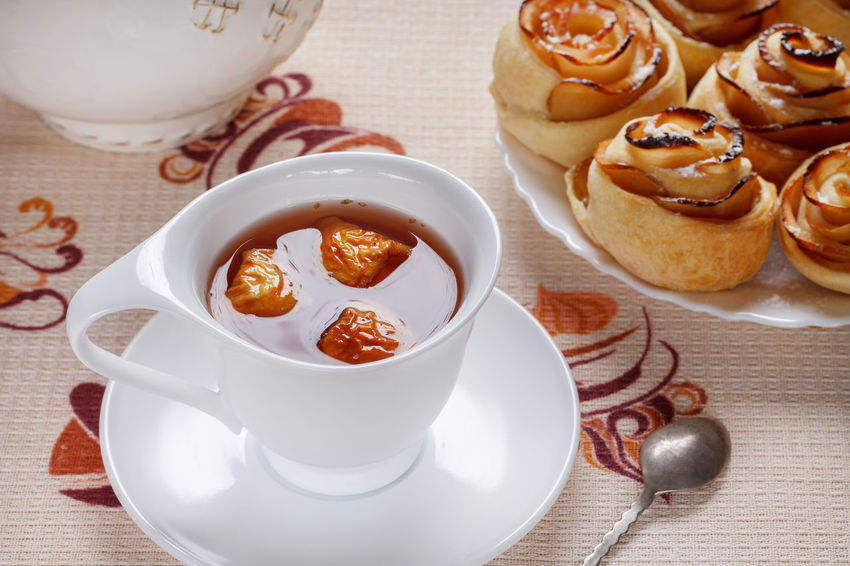 Herbal apple tea in a white cup with saucer and ruddy buns on a plate. Breakfast Appetizing Food Bowl Buns Close-up Day Dessert Food Food And Drink Freshness Healthy Eating Indoors  Napkin No People Plate Ready-to-eat Rosettes Sauce Sweet Food Table Tablecloth Teapot Teaspoon White