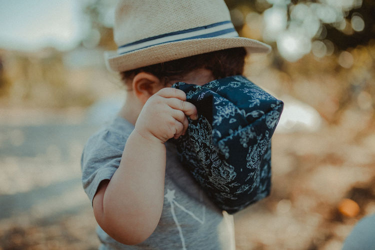 Close-up of baby boy holding bag