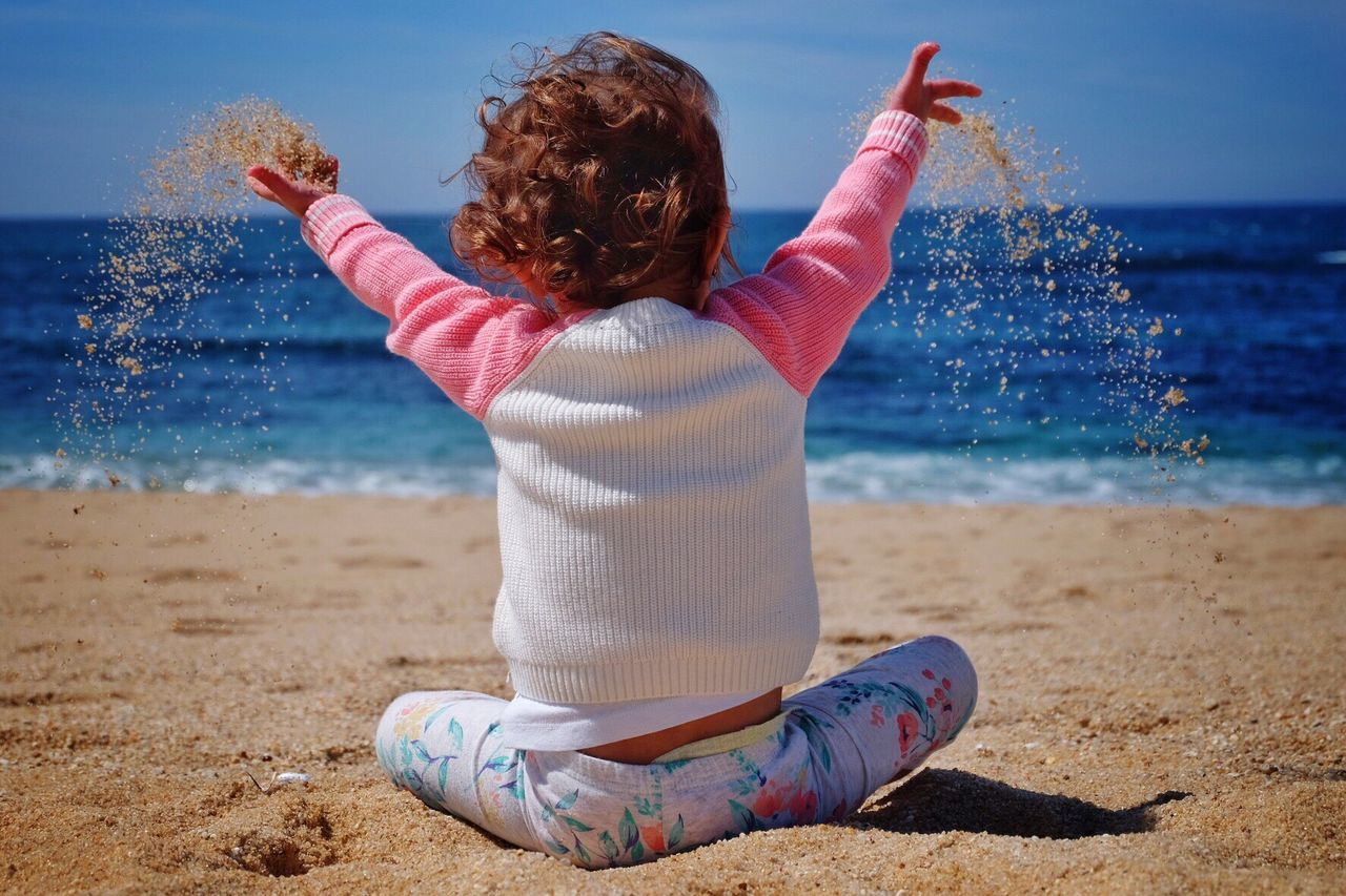Rear View Of Child Throwing Sand At Beach On Sunny Day