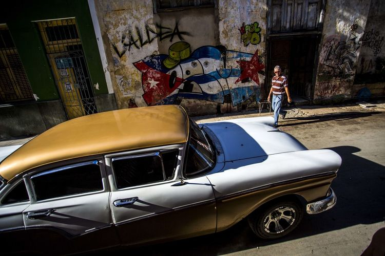 Car passes by Cuban flag on wall in street in Havana, Cuba. BestDestinatonSoFar Caribbean Life Cuban Flag Havana, Cuba Travel Architecture Beauty Beauty In Nature Bestdestinations Building Exterior Built Structure Car Cuban Life Day Full Length Land Vehicle Men Mode Of Transport One Person Outdoors People Real People Street Photography Streetphotography Transportation