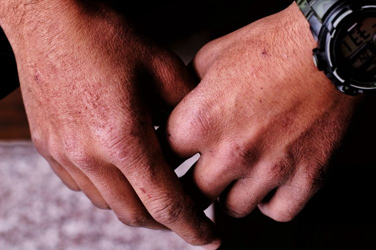 Cropped hands of man wearing wristwatch
