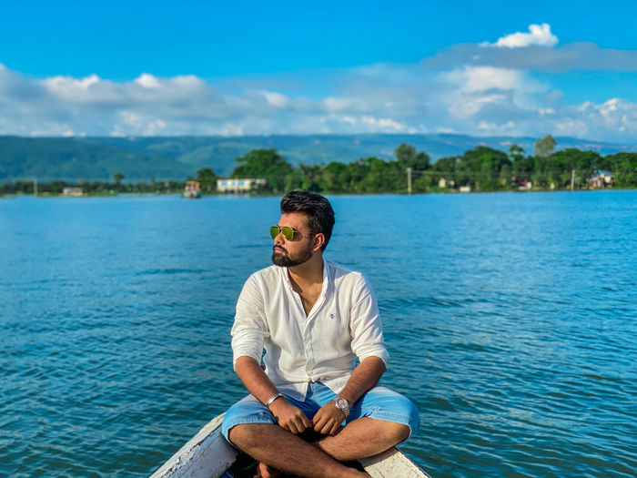 Young man sitting in sea against sky