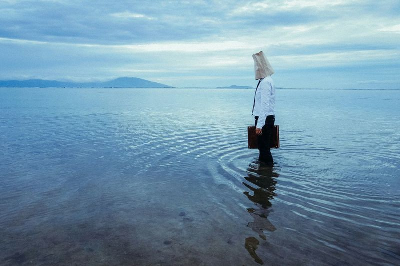Man standing on lake with covered face against cloudy sky