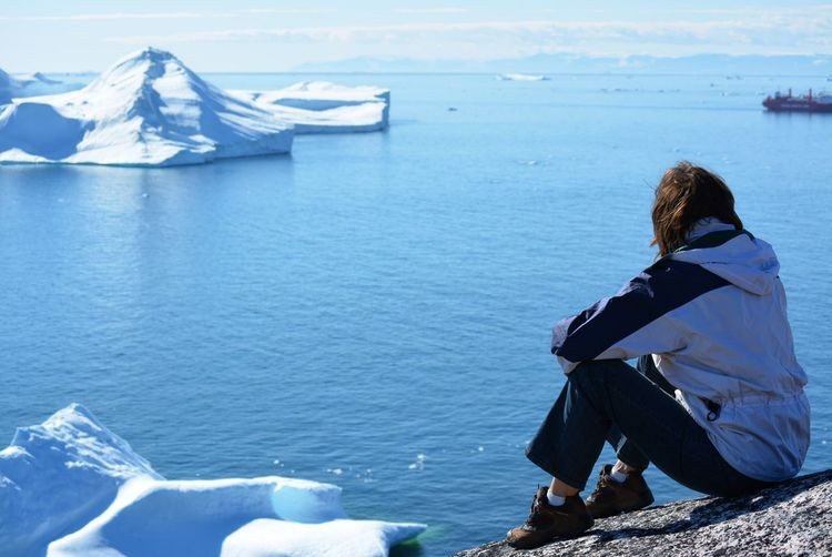 Ilulissat, Greenland, July | UNESCO world heritage site | impressions of Jakobshavn | Disko Bay Kangia Icefjord | huge icebergs in the blue sea on a sunny day | climate change - global warming Greenland Summer Day Nature Outdoors Hiking Travel Destinations Looking At View Holiday Tranquil Scene Women One Person Leisure Activity Scenics - Nature Real People Sitting Beauty In Nature Full Length Lifestyles Tranquility Rock Rock - Object Sea Water