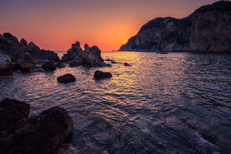 Beauty In Nature Cliff Corfu Greece Idyllic Majestic Nature No People Non Urban Scene Orange Color Outdoors Rock Rock - Object Rock Formation Sunset Tranquil Scene Tranquility Water