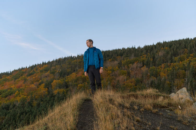 Low angle view of man standing on ridge against forest