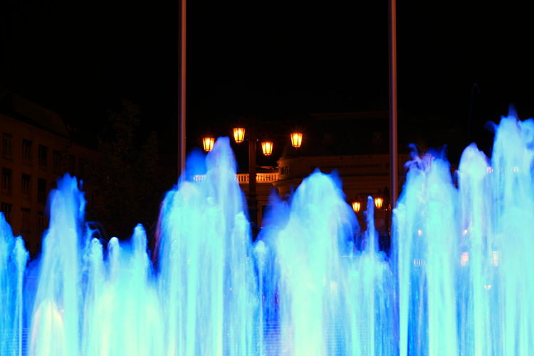 Adult Architecture Arts Culture And Entertainment Blue Blurred Motion Built Structure City Group Of People Illuminated Lifestyles Light Trail Long Exposure Medium Group Of People Motion Night Nightlife Outdoors People Real People Speed