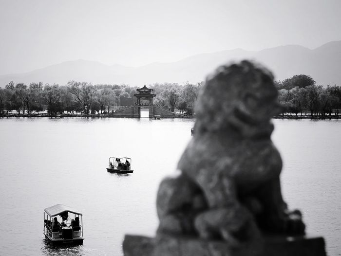 Statue by lake against clear sky
