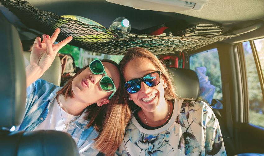 Portrait of happy friends wearing sunglasses while sitting in car