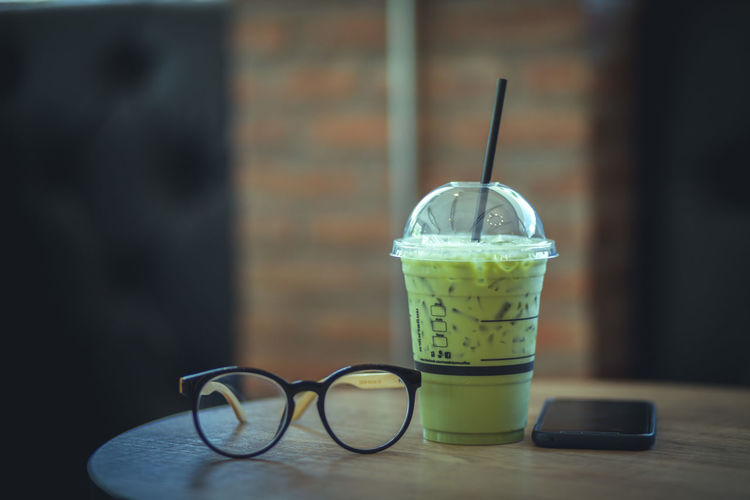 Eyeglasses And Drink By Mobile Phone On Table