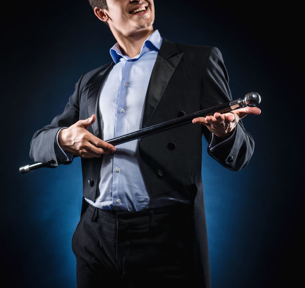 Man in elegant black jacket and blue shirt holding cane with silver ball handle Adult Artist Artistic Elegant Man Suit Wizard Adult Black Background Cane Handle Handsome Holding Jacket Magician Male One Man Only One Person People Perform Standing Stick Studio Shot Young Adult Young Men
