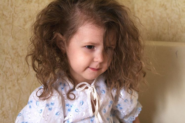Close-up of girl with wavy brown hair against wall