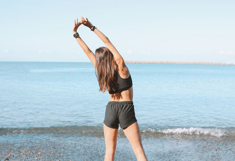 Rear view of woman exercising at beach