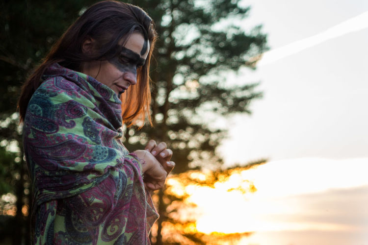 Side view of woman with black face paint wrapped in blanket during sunset