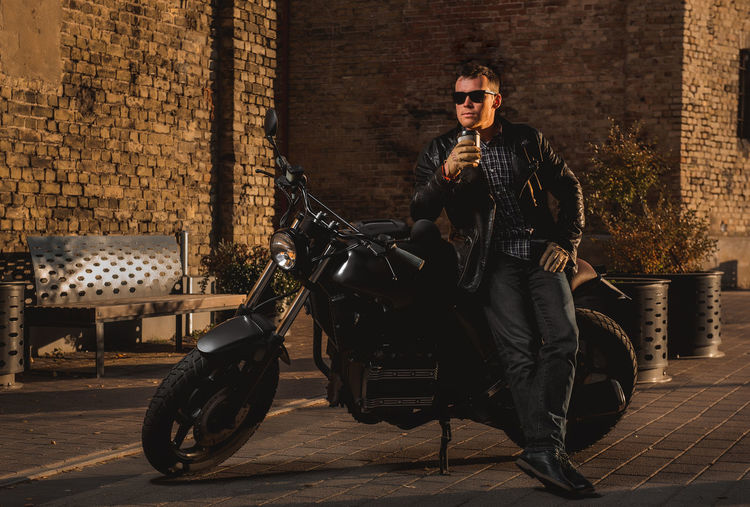 Man holding disposable cup while leaning on motorcycle parked against building