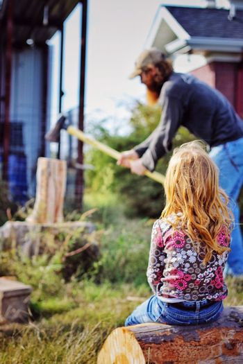 Fatherhood Moments Father Daughter Learning Watching Chopping Wood Ax Firewood Working Manual Farm Arkansas Focus On Foreground Person Long Hair Blond Hair Day Primary Age Child Outdoors Memories Business Stories The Photojournalist - 2018 EyeEm Awards