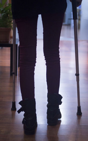 Low section of person walking with crutches