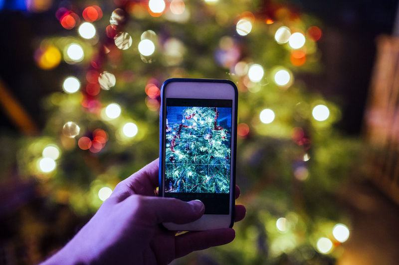 Cropped image of hand photographing christmas tree through mobile phone