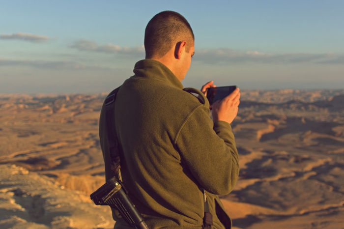 A young soldier taking a picture with his smartphone at Mitzpe Ramon in Israel. Nature Soldier Army Crater Environment Landscape Lifestyles Military Mobilephotography One Person Rear View Smartphonephotography Sundown Weapon