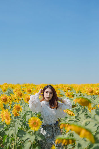 Young woman with yellow flowers on land against clear sky