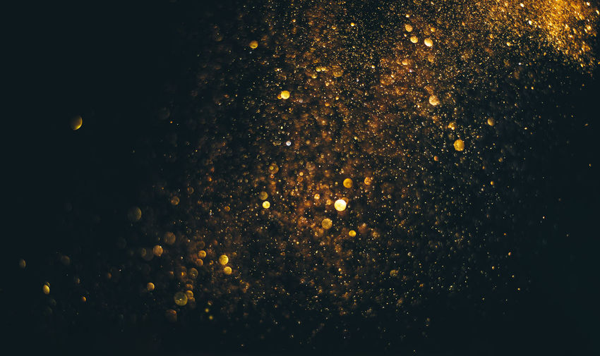 Close-up of gold glitter against black background