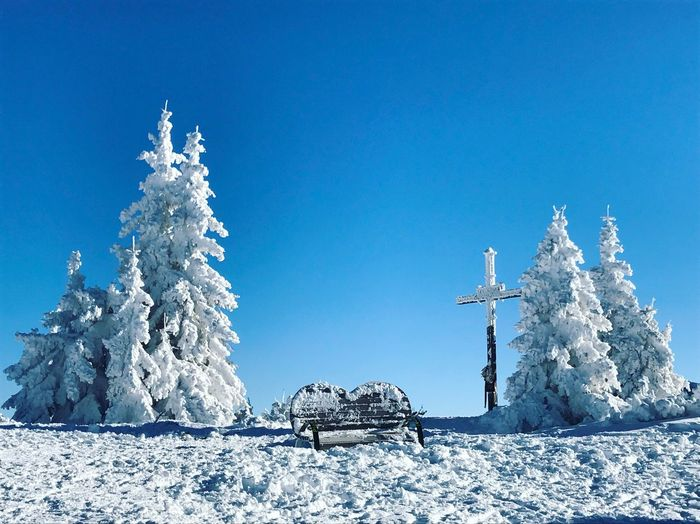 Snow on landscape against clear blue sky