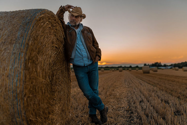 Full length of man standing on field against sky during sunset