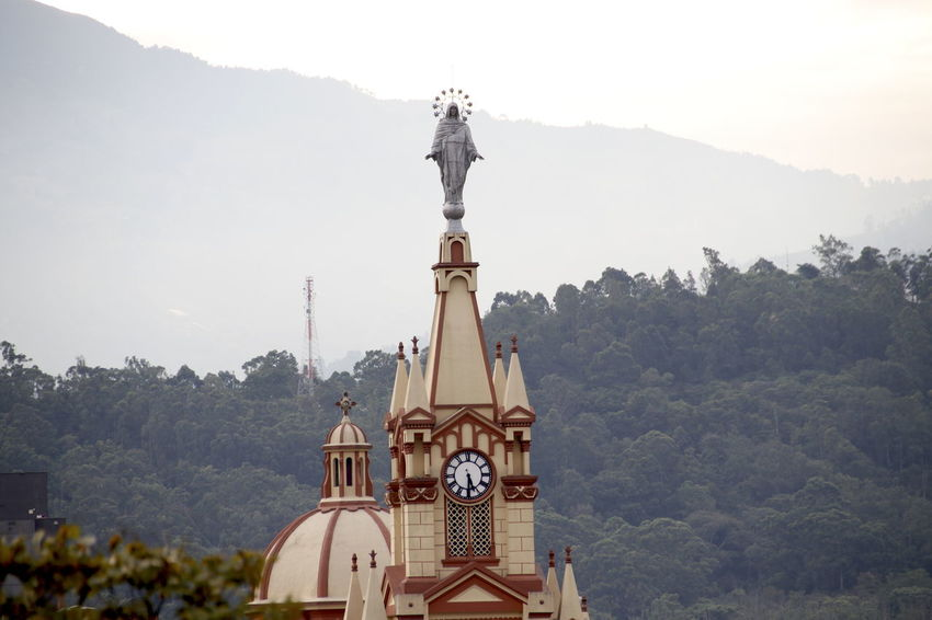 Medellín Virgin Mary Architecture Belief Building Building Exterior Built Structure Clock Day Holy Place Human Representation Mountain Nature No People Outdoors Place Of Worship Plant Religion Representation Saint Sculpture Sky Spirituality Travel Destinations Tree