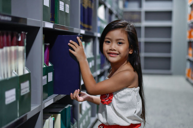 Smiling Girl Keeping Book In Shelf At Library
