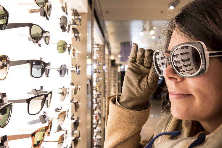 Close-up of woman shopping sunglasses in store