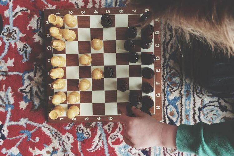 Cropped hand playing chess on bed