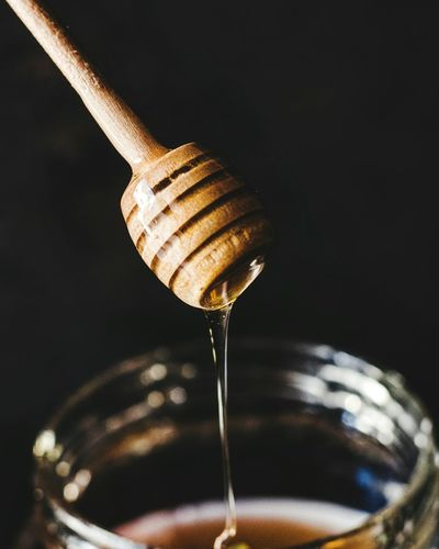Close-up of dipped pouring honey in jar